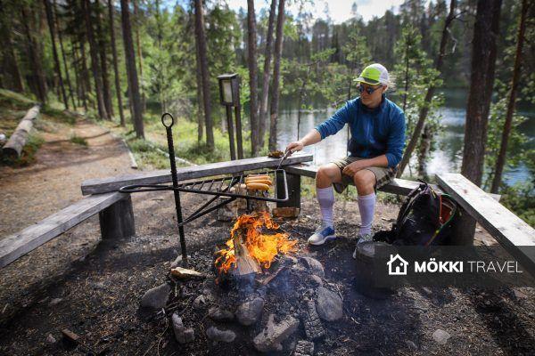man braadt worstjes boven vuur in Oulanka